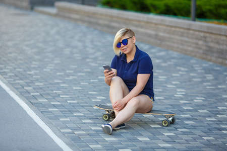stylish girl of large sizes, fashionable haircut in mirror glasses, sitting on a longboard against the background of the building, holding the phone