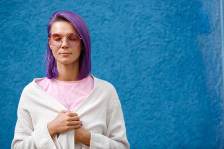 a girl with violet hair on a blue background closed her eyes, in pink glasses, calm, relaxed, holding a jacket in her hands, wrapped herself up