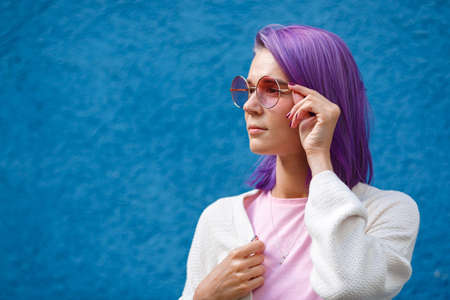 Beautiful young girl with purple hair in pink glasses on the blue background looks to the side, white jacket, hand holds glasses, red manicure 스톡 콘텐츠