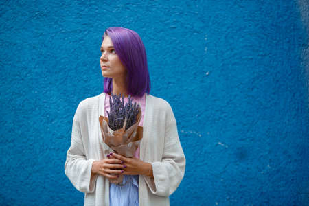 beautiful girl with violet hair on a blue background holding a lavender bouquet in her hands, looking away, horizontal frame, free space