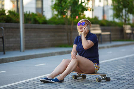 stylish girl of large sizes, fashionable haircut in mirror glasses, sitting on a longboard, talking on the phone, smiling