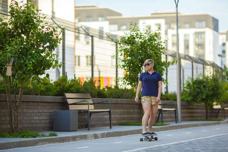 sporty stylish plussize girl in sunglasses rides a longboard along the tracksporty a path past trees and benches