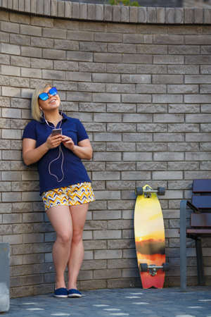 stylish girl of plus size, fashionable haircut in mirror glasses, headphones, smiling, holding a smartphone in her hands, longboard standing nearby, in full growth