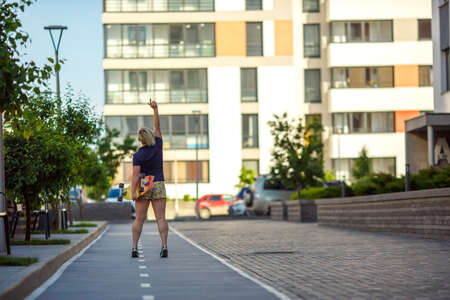 stylish girl plus size in a T-shirt and shorts with a longboard is standing back, hand boldly raised up against the background of building and trees