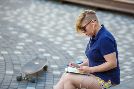 stylish girl plus size, fashionable haircut in mirror glasses, headphones, sitting outdoors, writes in a notebook, holding smartphone, longboard
