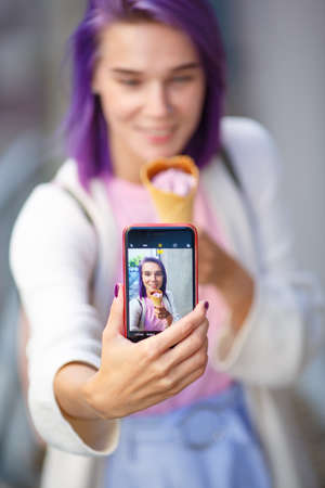 slim beautiful girl with purple hair shows her picture on the phone, there is ice cream