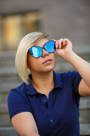 stylish girl plus size, fashionable haircut in mirror glasses is sitting on the steps and looking at the sky, blue T-shirt, summer, freedom, sports