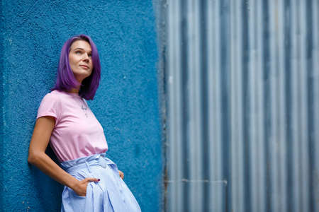 slim beautiful girl with purple hair on a blue background, is leaning on the wall of the building, looking up, smiling Stock Photo