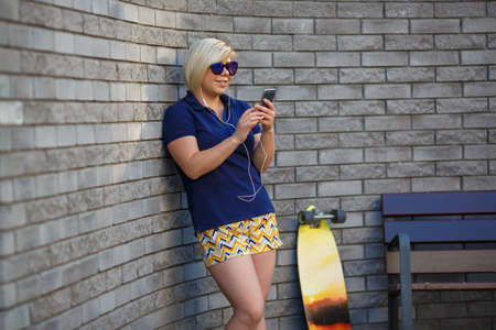 stylish girl of plus size, fashionable haircut in mirror glasses, headphones, smiling, holding a smartphone in her hands, longboard standing nearby Stock Photo