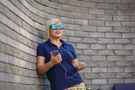 stylish girl of plus size, fashionable haircut in mirror glasses, headphones, smiling, holding a smartphone in her hands, Brick wall Stock Photo