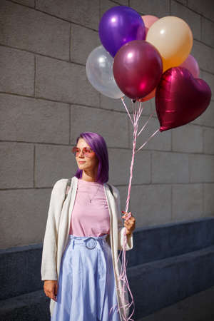 Girl with violet hair, in pink glasses, white blouse and blue skirt, looking to the right side and hold buch of helium airballoons in left hand in front of grey bricked wall background