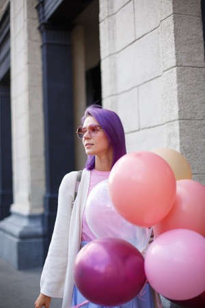 Young lady with violet hair pierced nose in pink glasses and white blouse with bunch of airballoons standing in front of gray bricked wall background