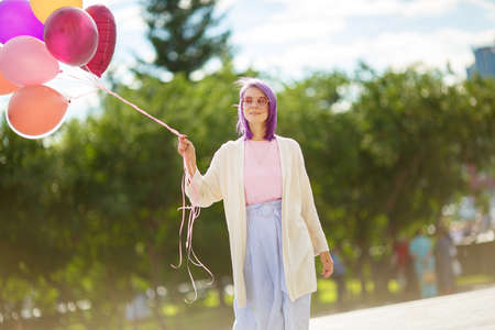 Young lady with purple hair, in pink glasses, white sweater pink t-short and blue skirt, with bunch of balloons in her right hand, standing outdoors in front of green trees background.