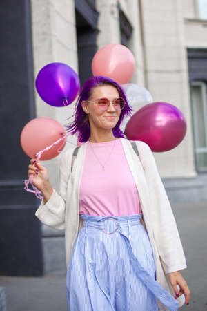 Woman with violet hair in pink spectacles, white blouse and blue skirt, smiling and walking on the street with bunch of airbaloons in her right hand in front of grey backgroung.