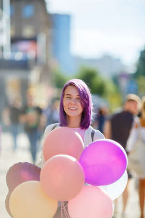 Girl with violet hair in white sweater standing in city street with helium baloons. and smiling. Sunny day in the city