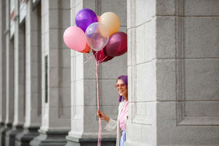 Girl with purple hair pierced nose in pink glasses, white blouse and pink t-short, looking around corner of grey bricked column holding bunch of helium baloons in her right hand and smiling