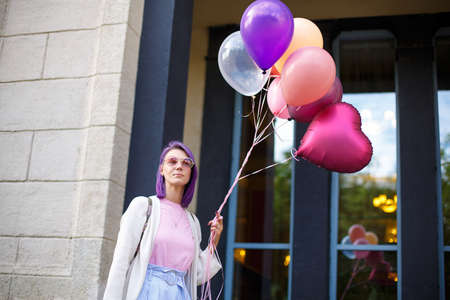 Woman with purple hair, in pink spectacles, white blouse and pink t-short, standing outdoor with bunch of airbaloons in her left hand in front of windowed background