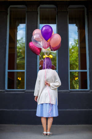 Young lady with purple hair, white blouse, blue skirt and sandals, standing turn her back with bunch of helium airbaloons in her right hand looking to window background Banco de Imagens