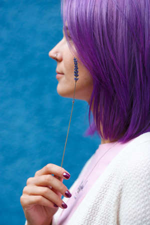 Portrait of a woman with colourfull purple hair, pierced nose in white cardigan turn her left profile with lavender stem in her right hand in front of blue background.