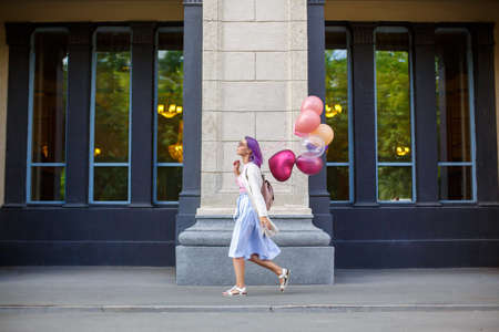 Young lady with purple hair in pink glasses, white blouse and blue skirt, walking outdoor with bunch of airbaloons, going to left side in front of grey bricked column and two windows background Banco de Imagens