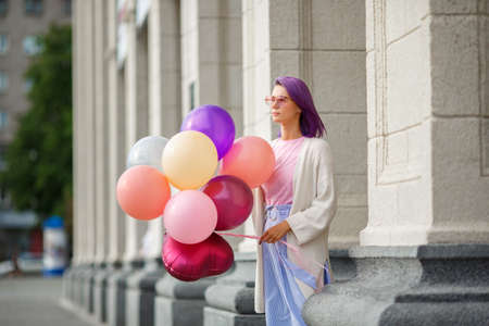 Female with violet hair in pink glasses white blouse, pink t-short and blue skirt, standing outdoor with bunch of baloons in her hand in front of grey bricked column background Banco de Imagens