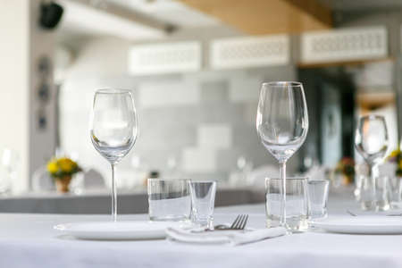 A front view of empty wine glasses and white dishes in the restaurant table set on white table cloth