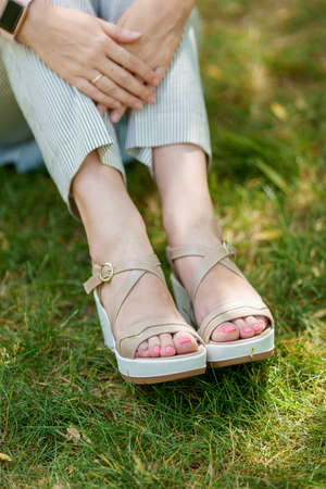 A closeup of womans feet in gray summer shoes and stripped pants are standing on the green grass