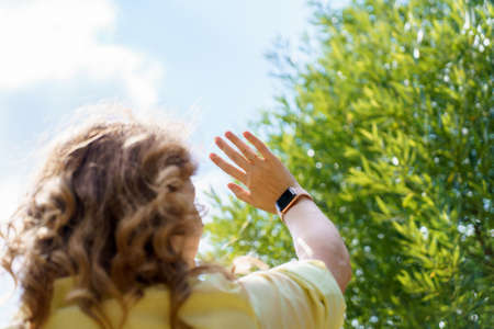 A young woman with red hair in yellow shirt lifted hand with watch up standing her back in summer day against tree in background