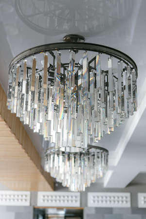 A two silver metal shining crystal chandelier on the ceiling one against another 版權商用圖片