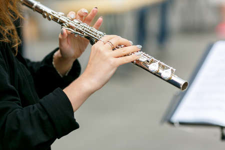 A closeup plane of street orchestra flautist with flute in her hands