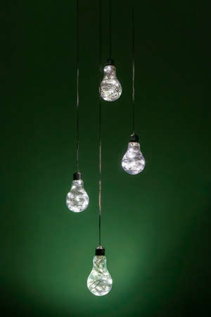 A foursome of amazing uncommon handmade electric lamps hanged in front of green background