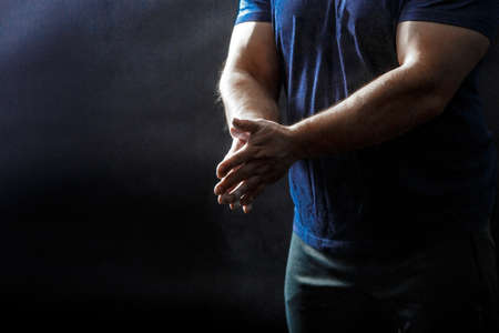 A part of males corpus, in black t-shirt with talcum powder covered hands squeezed together in front of dark background