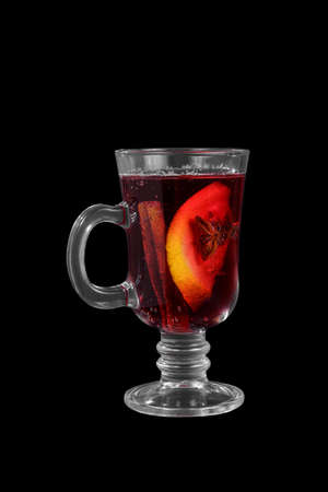 Monochrome transparent cocktail, red mulled wine in a high glass with a handle with spices and a slice of lemon, orange. Side view. Isolated black background. Drink for the menu restaurant, bar, cafe