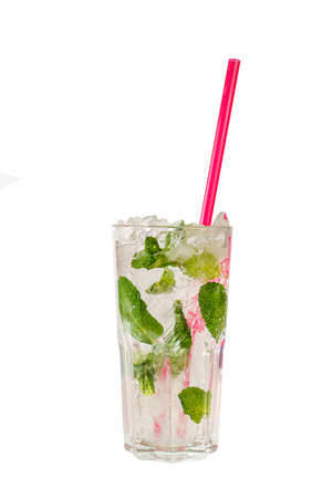 Summer drink with lime and mint leaves, frappe ice and pink straw in grain tall glass on isolated white background. Direct perspective, cool, refreshing