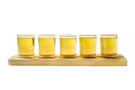 Yellow, same color opaque cocktails, a set of shots in one row, five servings on a wooden stand, substrate, side view Isolated white background. Drink for the menu restaurant, bar, cafe