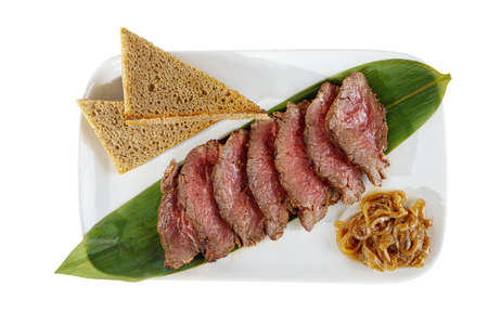 Cold appetizer before alcohol, food marinated roast beef, fried, beef, with pickled onions and bread, slices, 7 pieces on a banana leaf, on square plate, white isolated background view from above