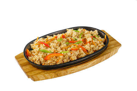 Vegetarian rice with vegetables, peppers, bell peppers, soy meat serving on a hot frying pan, on a wooden board on white isolated background side view. For the menu, restaurant, bar, cafe