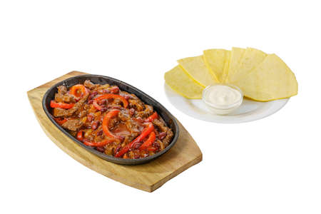 fajita, beans and bell peppers with meat, beef, lamb, tortilla and sour cream sauce, fried, baked portion on a hot frying pan, on a wooden board on a white background Side view. For the menu