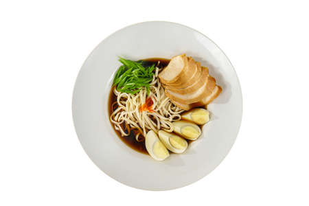 fo bo soup, with vegetables, noodles, greens onions, egg, chicken, spicy red sauce in a white plate isolated white. Serving dishes in a cafe, restaurant, for a menu, view from above Imagens