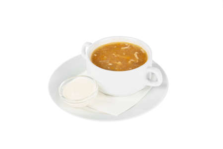 Soup with chicken, fish, cabbage soup, in plate isolated white and sour cream, on a napkin. Serving dishes in a cafe, restaurant, for a menu. Side view Imagens