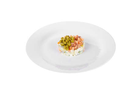 Russian salad with peas, red fish, chum salmon, eggs, cucumbers, carrots, potatoes on plate, side view white isolated background Imagens