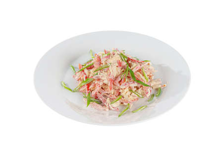 Salad with Bulgarian pepper, meat, chicken, squid, crab sticks, egg, mayonnaise, green onion on plate, white isolated background Side view. For the menu, restaurant bar cafe Imagens