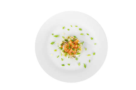 Russian salad with peas, red fish, chum salmon, eggs, cucumbers, carrots, potatoes, decorate green onion on plate, view from above, white isolated background Stock fotó