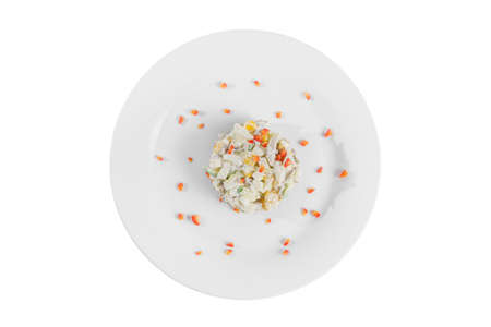 salad with corn, cucumber, meat, egg, mayonnaise, sour cream, garnished with bell pepper, potatoes on plate, view from above, white isolated background Imagens