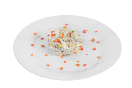 salad with corn, cucumber, meat, egg, mayonnaise, sour cream, garnished with bell pepper, potatoes on plate, side view white isolated background