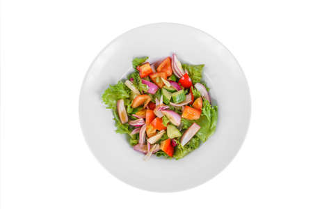 Vegetable salad with lettuce, red onion, cucumber, tomato, bell pepper, oil on plate, white isolated background, view from above. For the menu, restaurant bar cafe