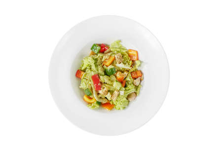 Caesar salad with pieces of chicken breast, tomato, bell pepper, cucumber, lettuce, walnuts on plate, white isolated background, view from above. For the menu, restaurant, bar, cafe Imagens