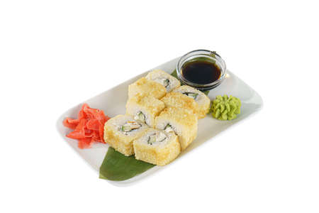 Sushi, rolls, uramaki Alaska, with avocado, cucumber, meat, soy sauce, marinated ginger and wasabi, on a banana leaf, white isolated background side view