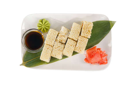 Sushi, rolls, uramaki Alaska, with avocado, cucumber, crab meat, raw seafood, soy sauce, marinated ginger and wasabi. Food on a banana leaf, white isolated background view from above Imagens