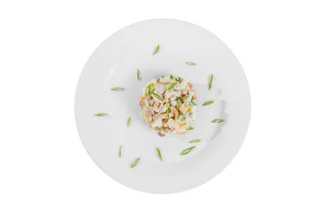 salad with mushrooms, honey mushrooms, cucumber, potato, bell pepper, sour cream, mayonnaise, garnished with green onions on plate, view from above, white isolated background